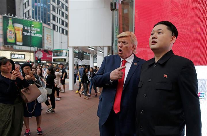 通りに集まった人の撮影依頼に快く応じるドナルド・トランプ米大統領(左)と北朝鮮の金正恩・朝鮮労働党委員長のそっくりさん=7日、香港(AP)
