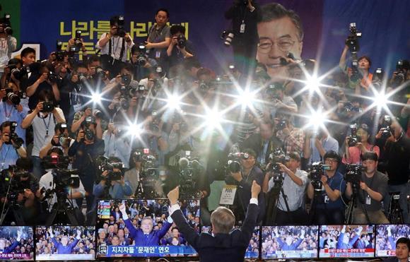 9日、出口調査で優勢が伝えられ、ソウルの国会内で報道陣に向かって両手を突き上げた文在寅氏(AP)