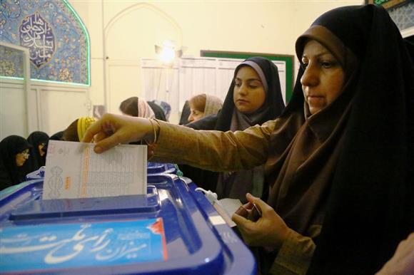 19日、テヘランで大統領選の投票をする女性(共同)