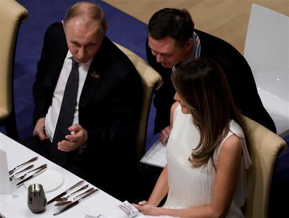 公式食事会の席で、ドナルド・トランプ米大統領のメラニア夫人に話しかける露のウラジーミル・プーチン大統領=7日、独ハンブルクのエルプフィルハーモニー・コンサートホール(ロイター)