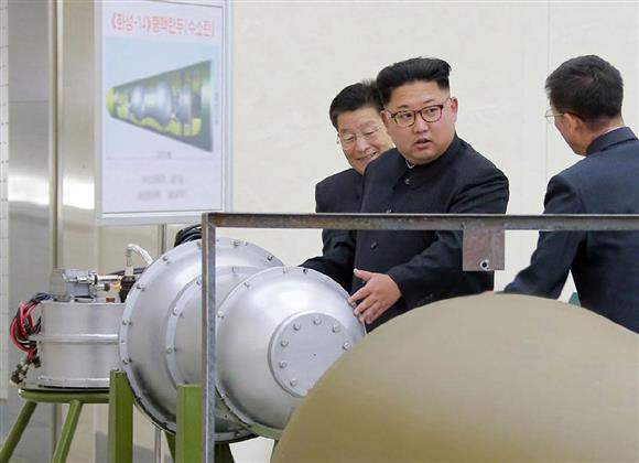 「火星14」型核弾頭と題された図面の前で「水爆」とみられる物体を視察する北朝鮮の金正恩朝鮮労働党委員長。朝鮮中央通信が3日配信した(朝鮮通信=共同)