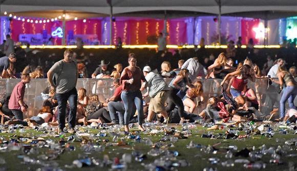 1日、米西部ネバダ州ラスベガスで銃乱射現場から逃げる人々(ゲッティ=共同)