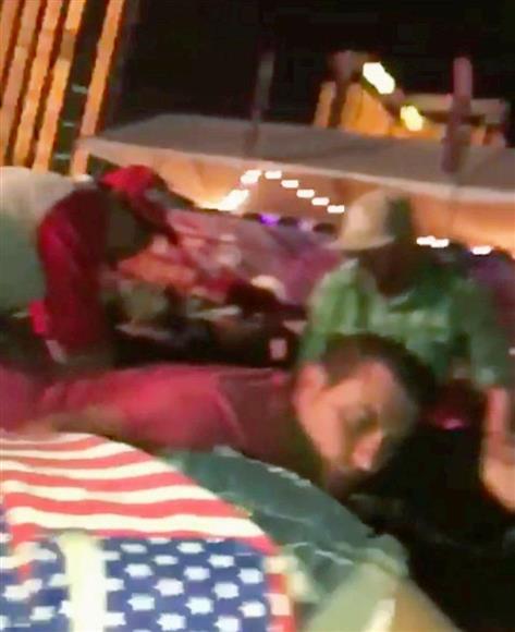 男がホテルから発砲する中、屋外コンサート会場でしゃがみ込む観客ら=1日、米西部ネバダ州ラスベガス(VINCESTAGRAMEN提供・ロイター=共同)