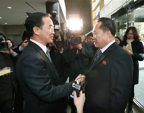 北朝鮮の祖国平和統一委員会の李善権委員長(右)と握手する韓国の趙明均統一相。この後、会談で北朝鮮は平昌冬季五輪への参加を正式に表明した=9日、板門店(韓国取材団・共同)