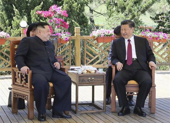 中国国営通信新華社が8日に配信した、中国遼寧省大連で会談する中国の習近平国家主席(右)と北朝鮮の金正恩朝鮮労働党委員長の写真(新華社=共同)